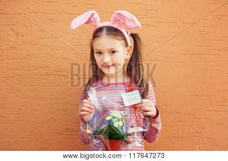 Cute little girl wearing rabbit ears, holding spring flowers in a pot