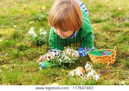 Adorable little blond boy playing with colorful easter eggs in the park,  egg hunting