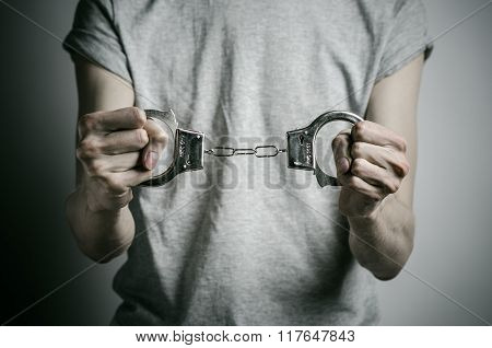 Prison And Convicted Topic: Man With Handcuffs On His Hands In A Gray T-shirt On A Gray Background I