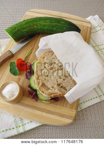 Cucumber sandwich in greaseproof paper bag