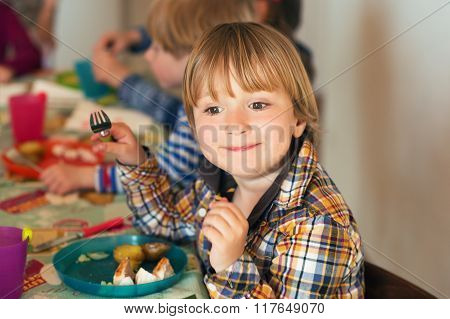 Adorable little boy having lunch with his friends