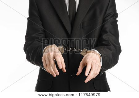 Corruption And Bribery Theme: Businessman In A Black Suit With Handcuffs On His Hands On A White Bac