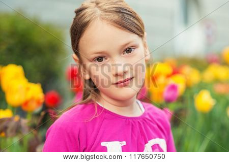 Outdoor close up portrait of adorable little girl of 7-8 years old