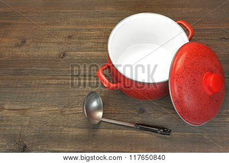 Red Empty Saucepan With Cover And Ladle On Wood Background