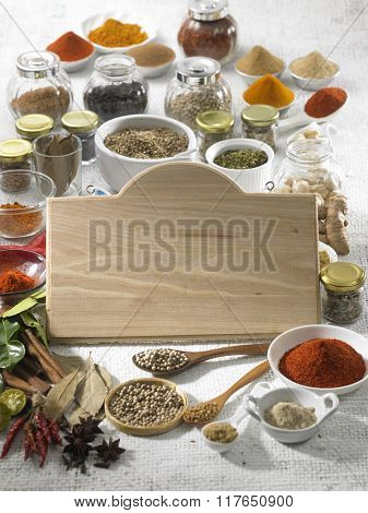 Blank wooden board on the assorted spices