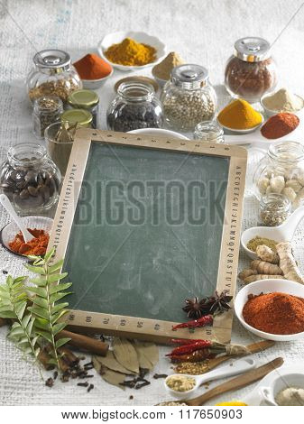 Blank blackboard with spices in the background.
