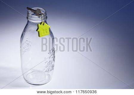 key with house shape key chain on empty jar