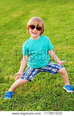 Fashion kid, cute little boy wearing turquoise shirt, blue shorts and shoes