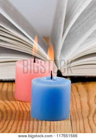 image of two candles on open book background closeup