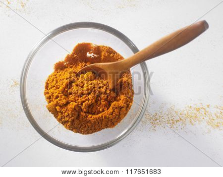 curry powder in a glass container with wooden spoon