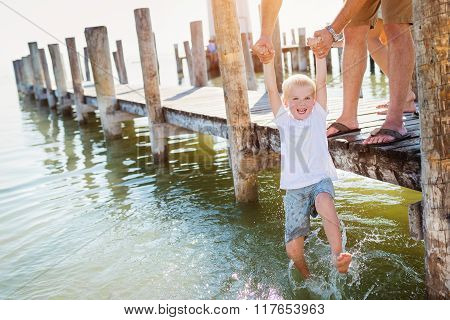 Father on the pier holding son above water, sunny summer