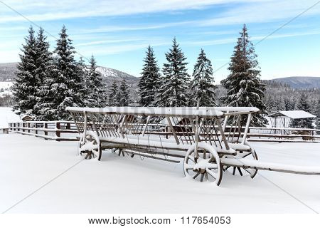 old wooden carriage in snow on winter meadow