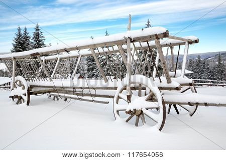 old wooden carriage in snow on winter meadow at nice day