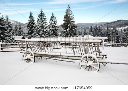 wooden carriage in snow on winter meadow