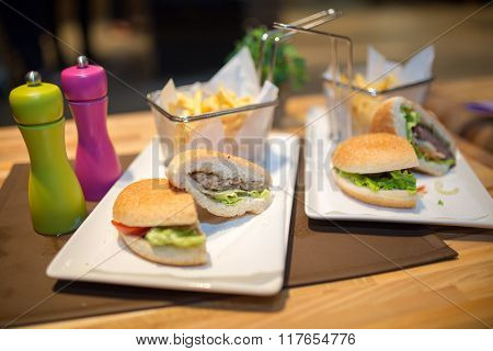 Hamburgers served with fries.Unhealthy,fatty food.Eating out junk food,fast food