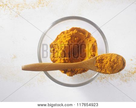 top view of curry powder in a glass container with wooden spoon