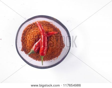 glass bowl of chili powder with chili padi