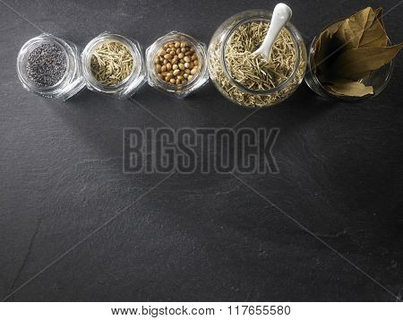 top view of assorted spices in a row on black slate