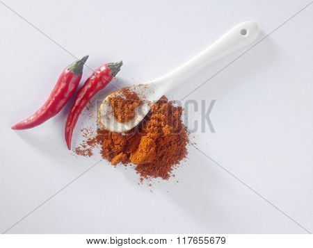 spoon of chili powder and chili padi on the white background