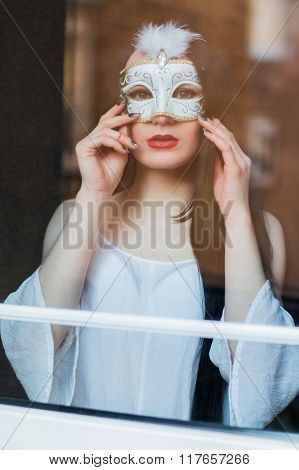 Portrait of beautiful mysterious young woman in carnival mask in front of the window