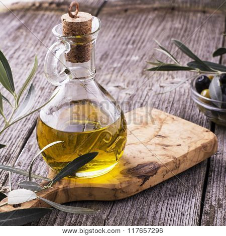 Jug with extra virgin olive oil on cutting board surrounded by branches