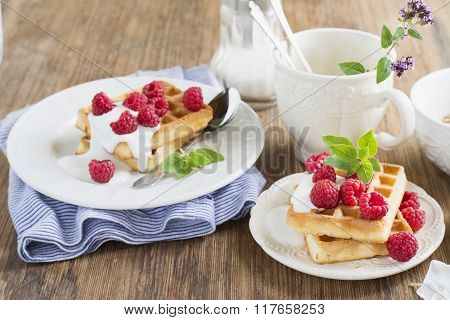 Golden homemade fresh waffles for breakfast with cream and raspberries