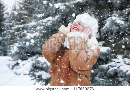Winter woman outdoor portrait with snow on head, snowy fir trees background