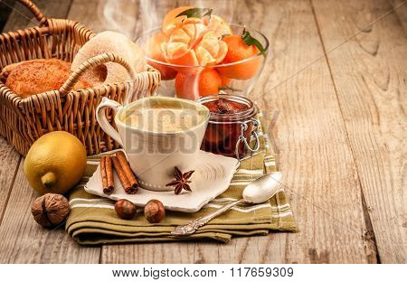 Hot morning coffee with smoke and breakfast. Fruits tangerines. Lemon and sweet jam on wooden board in rustic style
