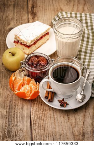 Morning breakfast with hot coffee and joghurt. Fruits tangerines. Lemon. Apple and sweet cake on wooden board in rustic style