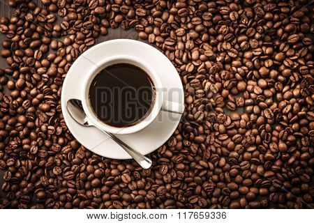 Coffee cup top view on beans background with spoon
