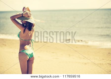 Beach woman enjoying summer and sun,walking the beach near clear sea.Summer feeling,happiness