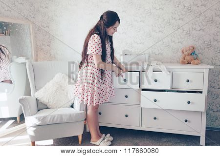 Home portrait of young pregnant woman preparing for childbirth and doing everyday homework at nursery