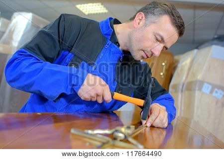 man hammering a crucifix