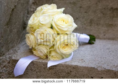 Wedding bouquet laid on a concrete stairs