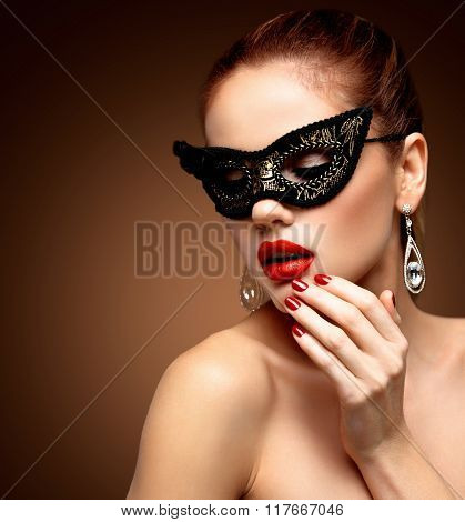 Beauty model woman wearing venetian masquerade carnival mask at party isolated on black background.