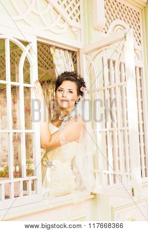 Young beautiful bride waits for groom near the window. Beautiful Bride lit by sunlight. beautiful yo