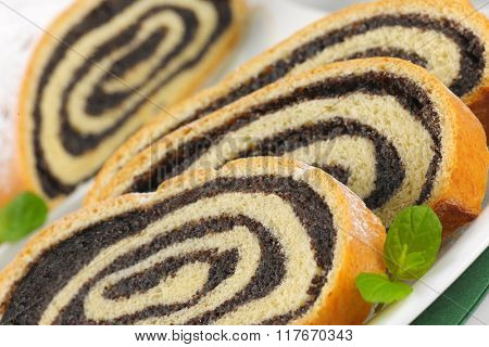 detail of sliced poppy seed roll on white plate