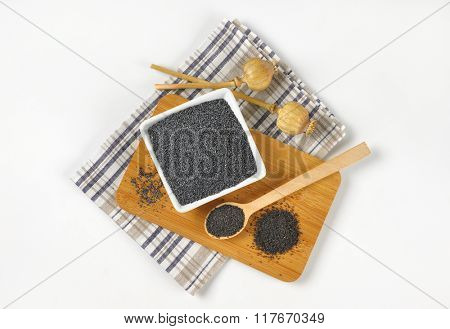 bowl of poppy seeds na poppy heads on wooden cutting board