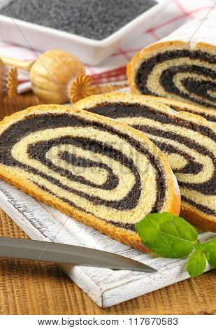 close up of sliced poppy seed roll on wooden cutting board