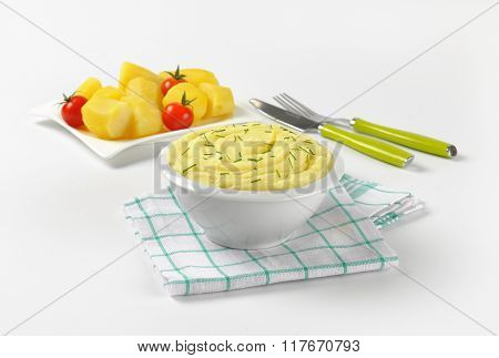 bowl of mashed potato puree with chopped chives on checkered dishtowel