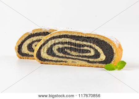 two slices of poppy seed roll on white background