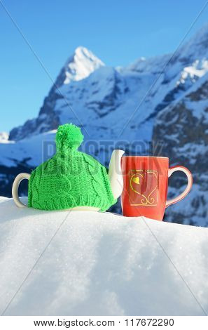 Tea pot in the cap and a cup against alpine scenery