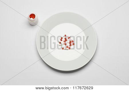 Medications And Improper Nutrition Topic: Human Hand Hold A Plate With Pills Isolated On White Backg