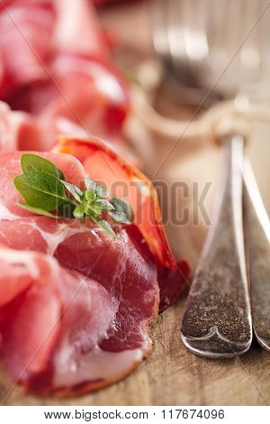 Cured Meat and vintage forks on textured Chalkboard and wooden background