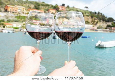 Two wineglasses in the hands against the harbour of Portvenere, Italy