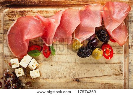 Cured Meat and ciabatta bread on wooden board on background