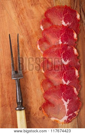 antipasti Platter of Cured Meat  jamon, vintage fork  and wooden background , closeup