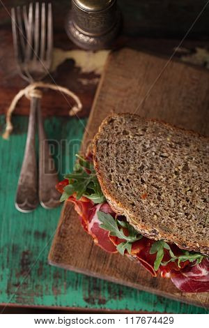 cured meat sandwich with seeded bread on old wooden table, shallow dof