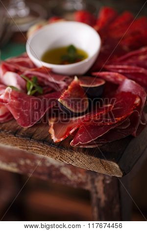 Cured Meat and olive oil on textured old wooden stool background