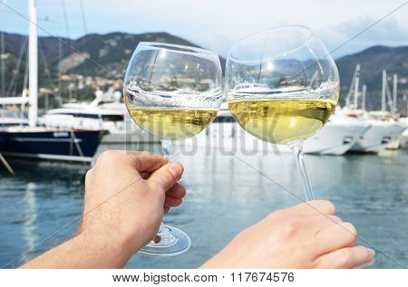 Pair of wineglasses in the hands against the yacht pier of La Spezia, Italy